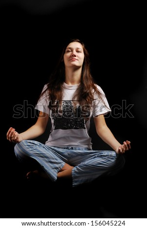 Happy teenage girl is sitting in the lotus position. She is wearing pajamas. Young woman is soaring in the dark.
