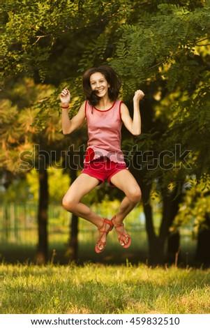 Happy teenage girl jumps - stock photo