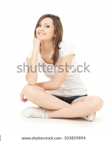 happy teenage girl sitting on the floor with crossed legs, full length, white background - stock photo