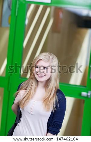 Happy teenage girl walking against door in school - stock photo