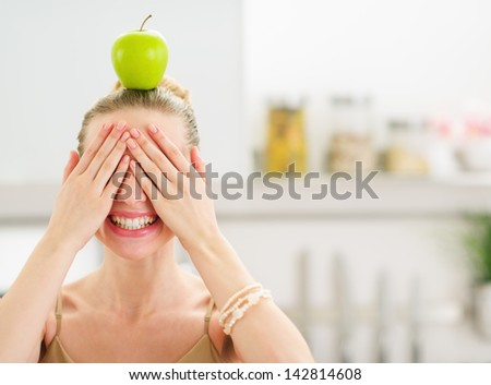 Happy teenage girl with apple on head closing eyes with hands - stock photo