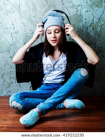 happy teenage girl with earphones, isolated against blue studio background - stock photo