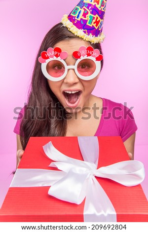happy teenage girl with gift box. pretty woman holding red box and wearing hat - stock photo