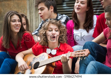 Happy teenage girl with guitar playing with a group of friends - stock photo