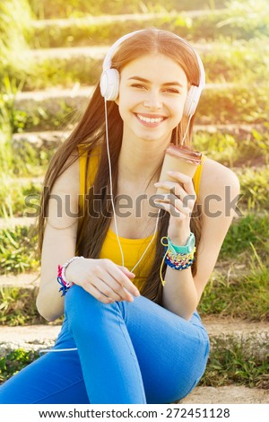 Happy teenage girl with headphones and takeaway coffee outdoors on sunny summer day. Beautiful millennial young woman listening to music. Vertical, retouched, vibrant colors. - stock photo
