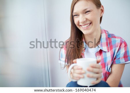 Happy teenage girl with mug in hands - stock photo