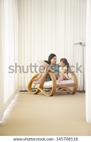 Happy teenage girl with sister relaxing on armchair at home - stock photo