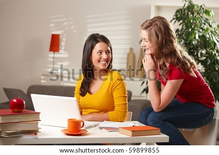 Happy teenage girls laughing together, sitting at table with laptop and books at home.? - stock photo