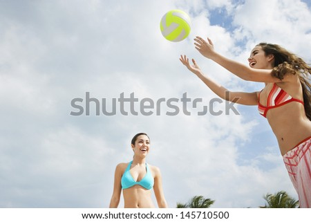 Happy teenage girls playing beach volleyball against cloudy sky