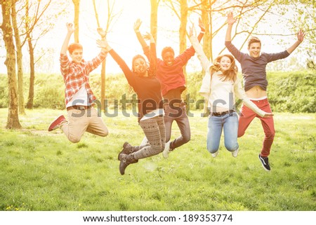 Happy Teenage Group Jumping Outside - stock photo