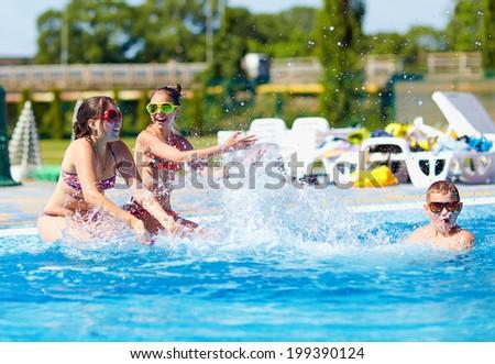 happy teenage kids splashing the water in pool - stock photo