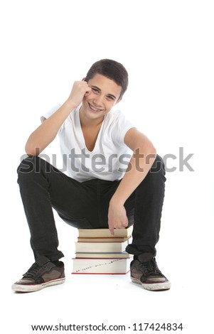 Happy teenage student sitting on a stack of his textbooks grinning with pleasure isolated on white
