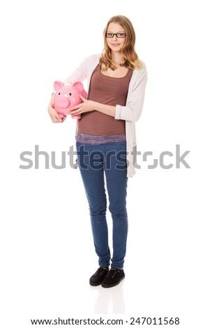Happy teenage woman holding piggybank - stock photo