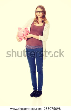 Happy teenage woman holding piggybank - stock photo