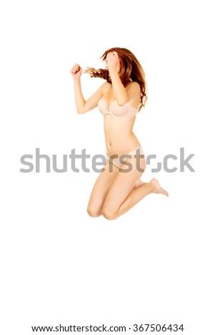 Happy teenage woman in underwear jumping  - stock photo