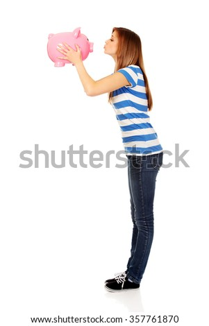 Happy teenage woman kissing a piggybank. - stock photo