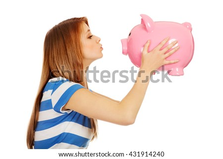 Happy teenage woman kissing a piggybank