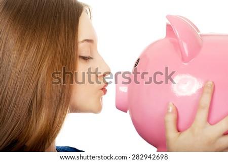 Happy teenage woman kissing piggybank. - stock photo