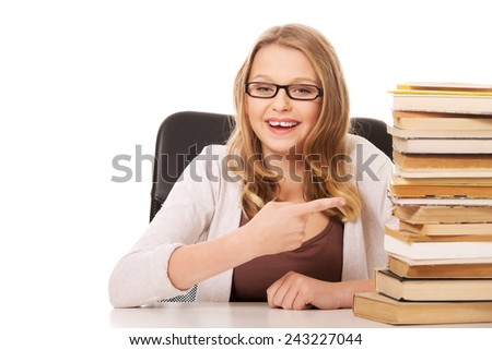 Happy teenage woman pointing on stack of books