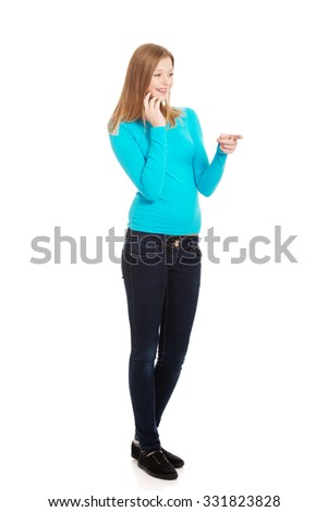 Happy teenage woman pointing to the left - stock photo