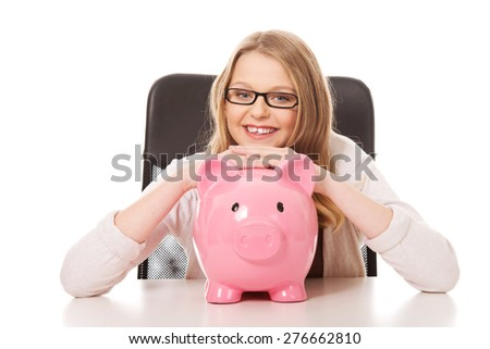 Happy teenage woman with piggybank on the table - stock photo
