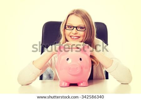 Happy teenage woman with piggybank on the table - stock photo