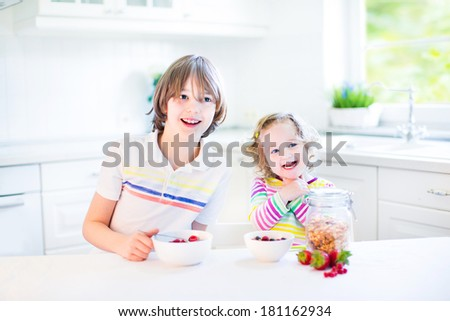 Happy teenager boy and his cute toddler sister having fruit and cereal with strawberry for breakfast before school and kindergarten drinking juice in a sunny white kitchen with a window