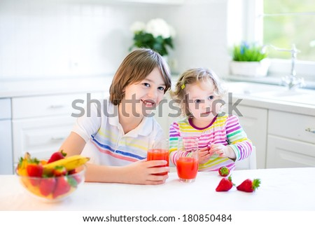 Happy teenager boy and his cute toddler sister having fruit for breakfast before school and kindergarten drinking juice in a sunny white kitchen with a window
