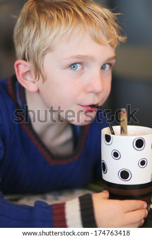 Happy teenager boy drinking milkshake cocktail from the straw sitting in the restaurant - stock photo