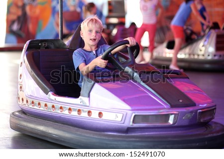 Happy teenager boy rides electric car during fan-fair entertainment - stock photo