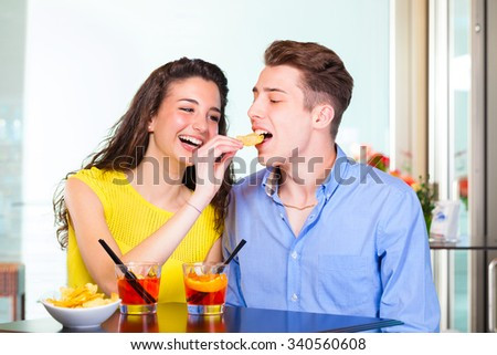 Happy teenager couple drinking cocktail and eating chips, sitting at table in the coffee bar