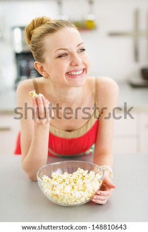 Happy teenager girl eating popcorn in kitchen