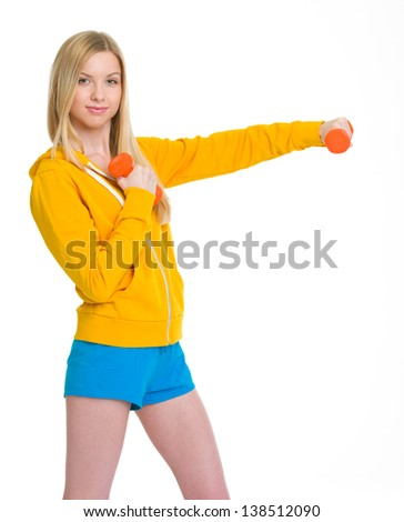 Happy teenager girl making exercise with dumbbells