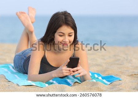 Happy teenager girl texting a smart phone lying on the sand of the beach - stock photo