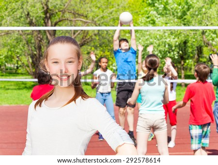 Happy teenager girl with team playing  volleyball - stock photo