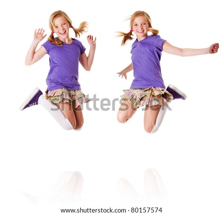 Happy teenager girls identical twins jumping and laughing of happiness having fun, isolated.