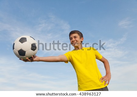 Happy teenager holds a soccer ball in his hands, on a background of blue sky