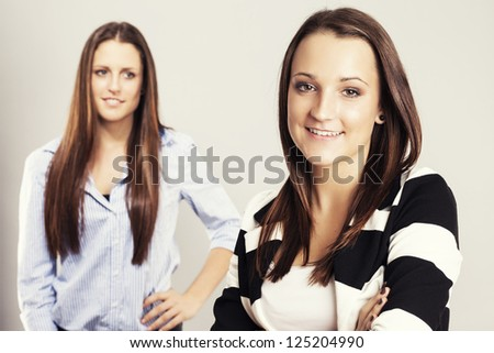 happy teenager in front of other brunette teenager - stock photo