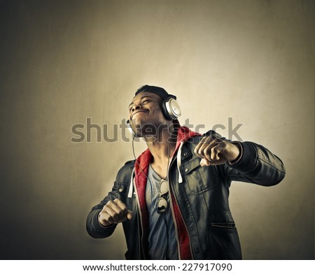 Happy teenager listening to music and dancing  - stock photo