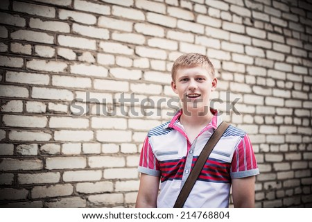 happy teenager on brick wall - stock photo