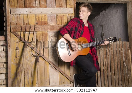 Happy teenager playing acoustic guitar concept, leaning on old wooden barn door
