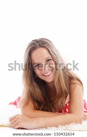 Happy teenager relaxing on a carpet Happy young teenager with a vivacious smile relaxing on a carpet lying on her stomach looking at the camera