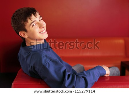 happy teenager sitting on the red sofa in home interior