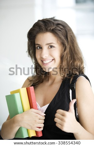 Happy teenager student with books