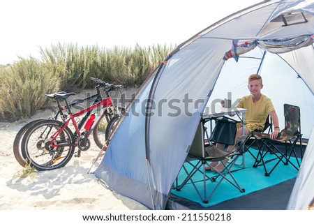 Happy teenager (teen) is sitting in the tent with bicycles at the beach. Young caucasian boy having fun and smiling in the camping trip. Active male model. Travel (vacations) and adventure concept.  - stock photo