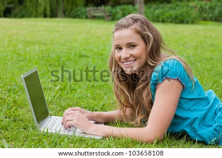 Happy teenager using her laptop while lying in a park and looking at the camera