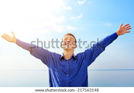Happy Teenager with Hands Up on the Sea background - stock photo