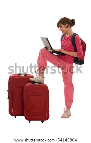 Happy teenager with huge luggages besides her, haversack on the back and laptop - stock photo