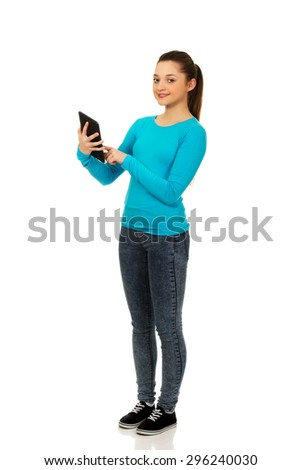 Happy teenager woman using a tablet. - stock photo