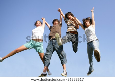 Happy teenagers jumping in the air - stock photo